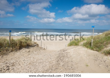 beach with sand dunes and a path to the sea - stock photo