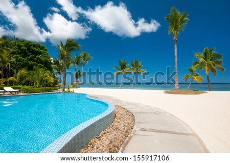 Beach with tropical pool - stock photo
