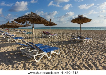 Beach with umbrellas and deckchairs, blue sky. Sunny day on vacation in Tunisia - stock photo