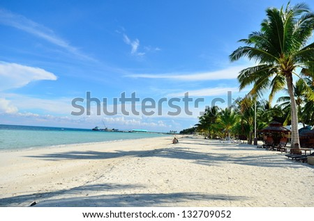 Beach with white sand, blue skies and coconut trees