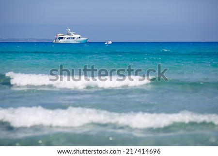Beach with yacht and kitesurfer in Sardinia