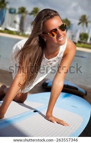 Beach woman at surfboard rental surf shop. Happy girl trying surf board on famous Waikiki beach, Honolulu City, Oahu, Hawaii, USA. - stock photo