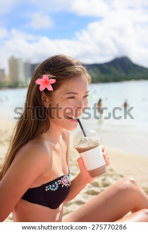 Beach woman drinking iced coffee cappuccino drink enjoying beach lifestyle smiling happy on Waikiki, Honolulu, Oahu, Hawaii, USA. Mixed race Asian Caucasian female in bikini. - stock photo