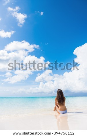 Beach woman enjoying serene luxury vacation relaxing under the sun sitting in water looking at perfect turquoise ocean at tropical getaway paradise. Girl from the back sunbathing. - stock photo
