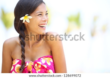 Beach woman happy looking to side laughing having fun smiling joyful and elated wearing sarong and flower on Hawaii. Multiracial Asian / Caucasian girl. - stock photo