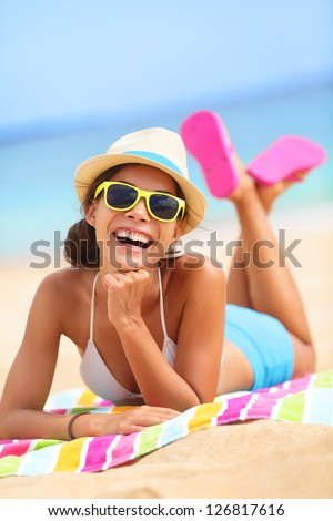 Beach woman laughing having fun in summer vacation holidays. Multiracial fashion hipster wearing sunglasses lying in the sand on colorful beach towel. - stock photo