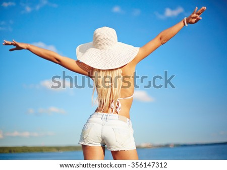 Beach woman standing with arms outstretched against sea and blue sky
