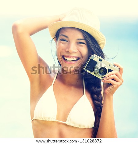 Beach woman with vintage retro camera having fun playful laughing in bikini on blue ocean background wearing beach hat. Multicultural Asian / Caucasian girl. - stock photo
