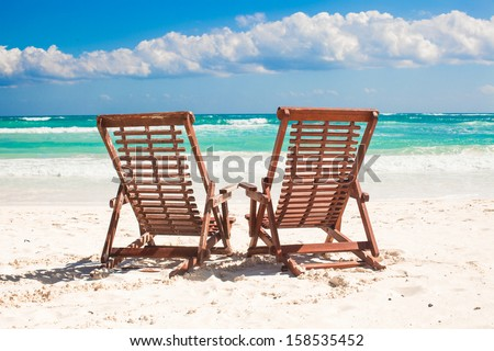 Beach wooden chairs for vacations and relax on tropical white sand beach in Tulum, Mexico - stock photo