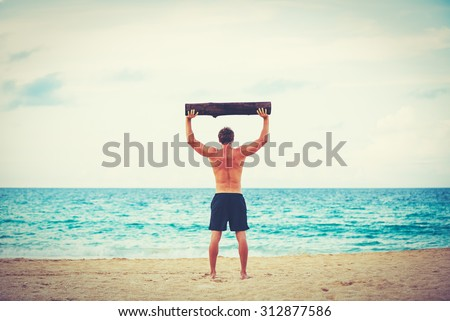 Beach workout. Male athlete exercising outdoors at the beach with tree log. Fitness and healthy lifestyle.