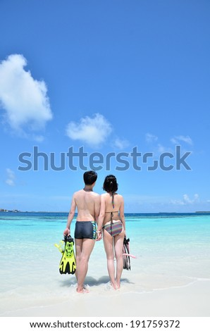 Beach young couple ready to go snorkeling -- Summer holidays concept  - stock photo