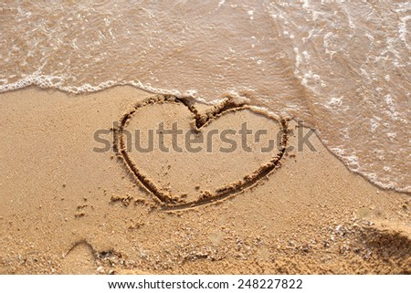 Beaches waves and heart shape drawn in the sand.