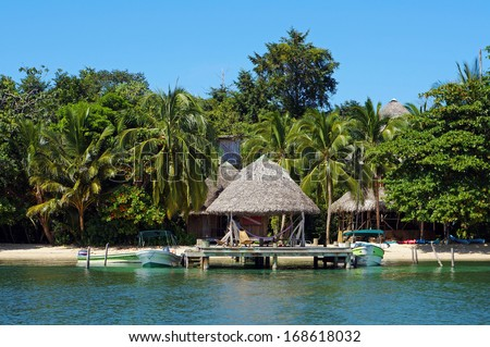 Beachfront eco resort with thatched hut over water and tropical vegetation, Caribbean sea, Bocas del Toro, Panama - stock photo