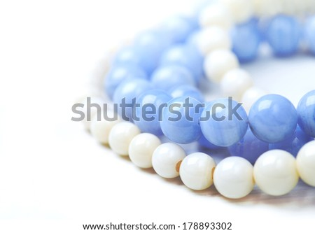 bead necklace made from blue agate and white coral on a white table, close-up, selective focus on some beads - stock photo