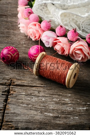 Beads and spool of thread, piece of lace on textured wooden background - stock photo