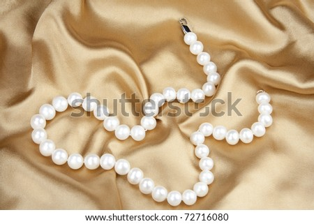 Beads from pearls on gold silk
