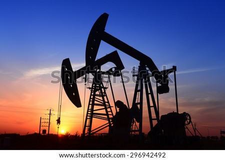 Beam pumping unit is operations in oilfield under the sun  - stock photo