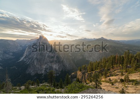 Beams of the sun make the way through Half Dome peak. Sierra Nevada mountains, Yosemite National Park, California