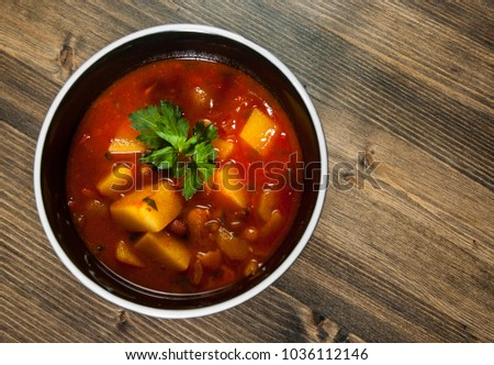 Bean and vegetables soup in ceramic bowl on wooden table. with copy space. top view