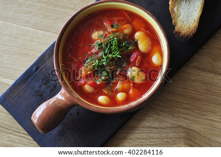 Bean soup in bowl on wooden table - stock photo