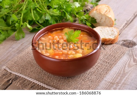 Bean soup in ceramic bowl on wooden table - stock photo