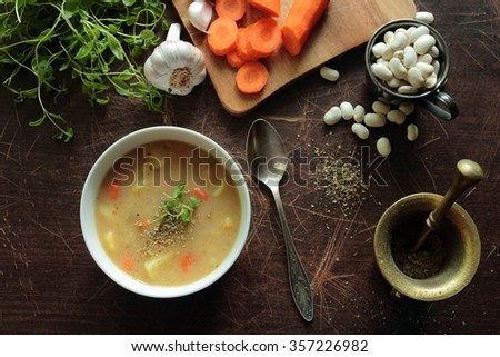 Bean soup with herbs and fresh ingredients - stock photo