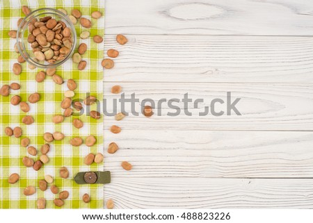 Beans in a glass bowl with on old wooden table. Top view.