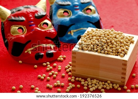 Beans in a wooden box with two masks behind them. - stock photo