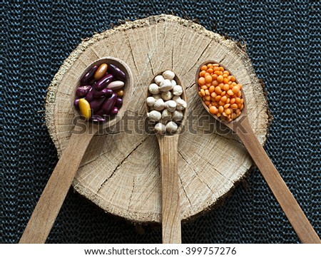 beans lentils chickpeas in wooden spoons on wooden background - stock photo