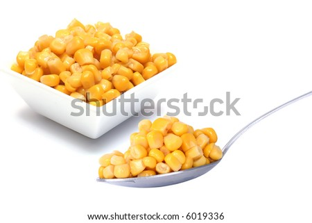 Beans of corn in vegetable dish and on the spoonful - stock photo
