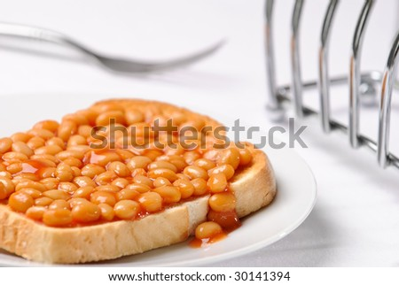 Beans on toast with fork and toast rack in background - stock photo
