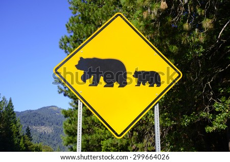 Bear crossing warning road sign in the wilderness - stock photo