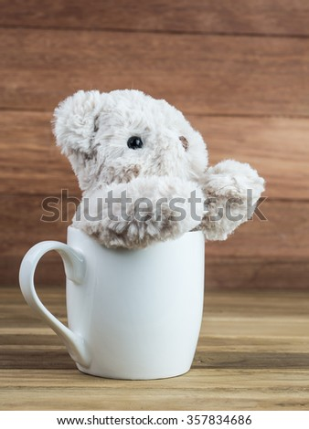 Bear doll in white cup.