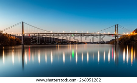 Bear Mountain Bridge at dusk. Bear Mountain Bridge is a toll suspension bridge in New York State, carrying U.S. Highways 202 and 6 across the Hudson River - stock photo