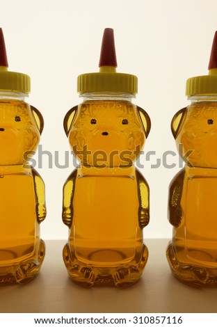 Bear shaped containers filled with honey. - stock photo