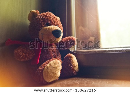 Bear toy sitting by the window - stock photo