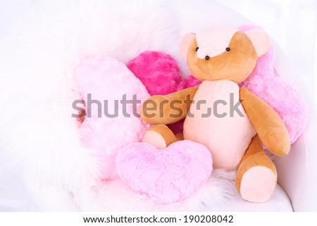 Bear toy with pillows on armchair in room