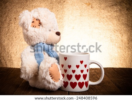 bear with a cup with hearts on the background of sacking - stock photo
