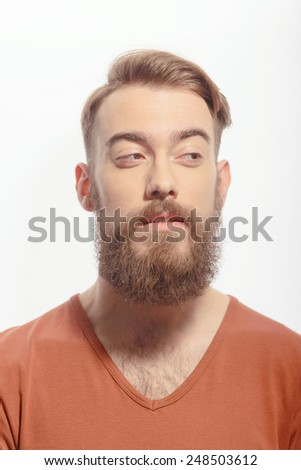 Beard and trendy. Closeup portrait of handsome bearded man wearing orange tshirt and looking away at copy space while standing against white background - stock photo