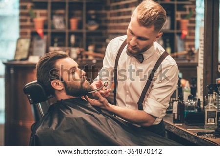 Beard grooming. Side view of young bearded man getting beard haircut by hairdresser while sitting in chair at barbershop - stock photo