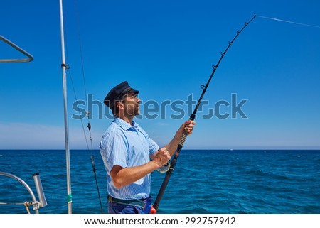 Beard sailor man fishing rod trolling in saltwater in a boat trolling with captain cap - stock photo