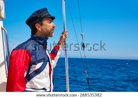 Beard sailor man sailing sea ocean in a boat with captain cap - stock photo