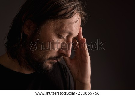 Bearded adult man with migraine headache, low key portrait