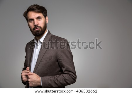 Bearded businessman in suit over grey background. Mock up
