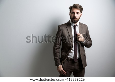 Bearded businessman in suit standing against grey wall. Mock up