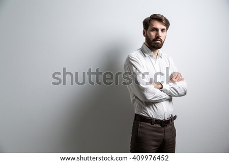 Bearded businessman in white shirt standing against blank wall with his arms crossed. Mock up - stock photo