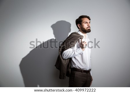 Bearded businessman in white shirt with suit jacket on shoulder standing against wall with shadow - stock photo