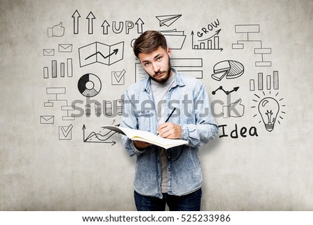 Bearded businessman with a notebook is standing near a concrete wall with a startup idea sketch
