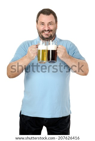 Bearded cheerful chap in blue polo t-shirt holding light and dark beer tankards on white background - stock photo