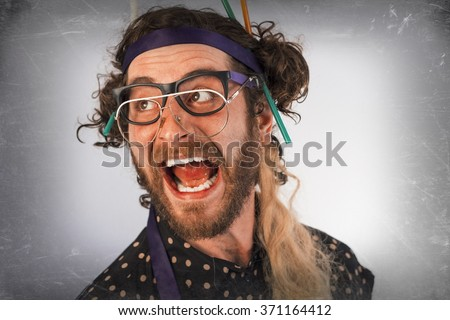 Bearded crazy person lunatic wearing several pairs of glasses - stock photo
